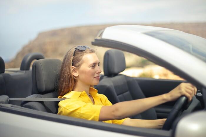 Jonge vrouw aan het autorijden in cabrio