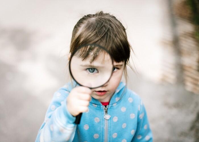 Meisje dat door een vergrootglas naar de camera kijkt