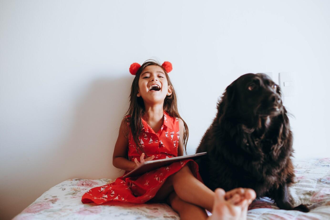 Lachend meisje in rood jurkje met een hond naast haar en een tablet op haar schoot